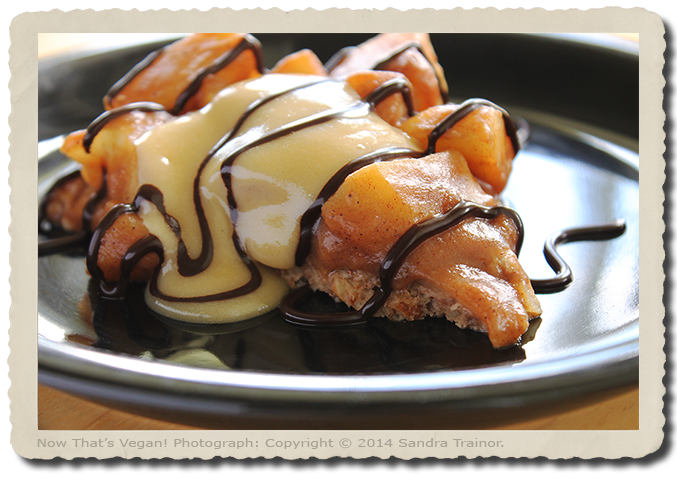 A vegan and gluten-free apple pie with a nut crust, vanilla cream, and chocolate sauce.