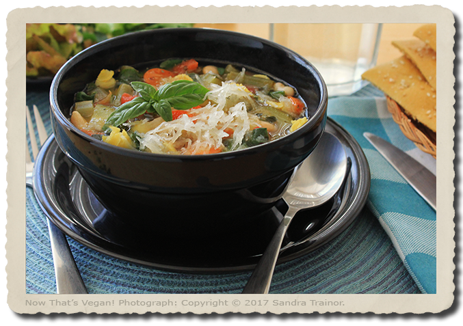 A hardy soup containing vegetables, gluten-free pasta, and beans.